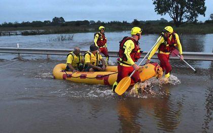 Een reddingsteam van de brandweer redt twee mannen die werden verrast door de overstroming uit een auto in de buurt van Brisbane.beeld EPA, Darren England