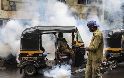 Een medewerker van de gemeente spuit in Mumbai, India, een bestrijdingsmiddel om te proberen elke vorm van ziekten veroorzaakt door muggen, waaronder malaria, te voorkomen. beeld EPA, Divyakant Solanki