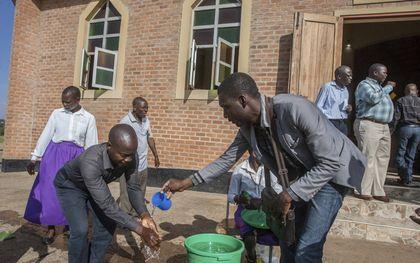 """""""Een studie toont aan dat er volop verspreiding van het coronavirus is in landen als Zambia en Malawi."""" Foto: Malawiaanse kerkgangers wassen hun handen tegen verspreiding van corona. beeld AFP, Amos Gumulira"""