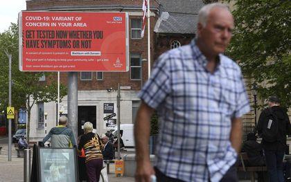 Een wandelaar passeert een waarschuwingsbord in Blackburn, Noordwest-Engeland. De Britse overheid stelt verder versoepelen van de coronaregels vier weken uit vanwege de zorgelijke deltavariant uit India.beeld AFP, Oli Scarf