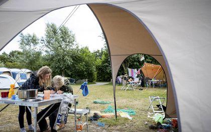 Jonge kampeerders vermaken zich bij hun tent op een natuurcamping van Staatsbosbeheer op Terschelling.beeld ANP, Sem van der Wal