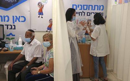 In Israël kunnen zestigers al om een derde dosis van het Pfizervaccin. Op de foto: een Israëlisch stel wacht op de derde prik bij de Clalit Health Service in Jeruzalem op 1 augustus 2021. beeld AFP, Menahem Kahana