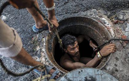 Een dalit maakt een riool schoon, zonder veiligheidsmaatregelen.beeld EPA, Rajat Gupta