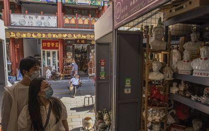 Op de antiekmarkt in Peking passeren mensen de buste van de Chinese president Xi Jinping en van zijn voorganger Mao Zedong. Steeds vaker worden beide leiders in een adem genoemd.beeld EPA, Roman Pilipey