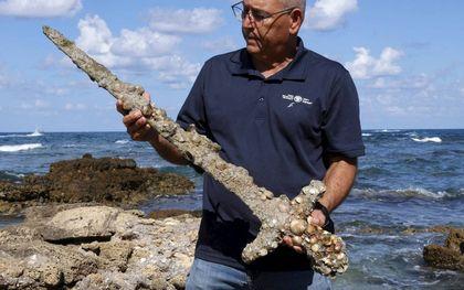 De amateurduiker Shlomi Katzin deed zaterdag een bijzondere vondst. Van de zeebodem bij het Israëlische Haifa dook hij een 900-jaar oud zwaard op. Het is hoogstwaarschijnlijk van een kruisvaarder geweest, zo melde de Israëlische Oudheidkundige Dienst dinsdag. De edelman die het zwaard droeg moet groot en sterk zijn geweest gezien het gewicht en de lengte van het zwaard, zei archeoloog Jacob Sharvit woensdag. Het wapen zit nu onder de schelpen. Deskundigen gaan het zwaard schoonmaken en verder onderzoeken.beeld AFP, Jack Guez