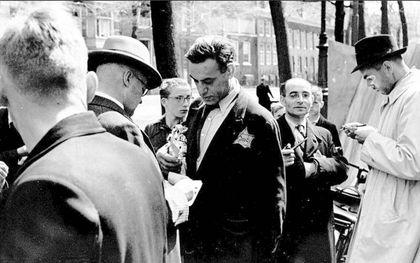 Nederlandse medewerkers van de SD controleren in de zomer van 1942 de persoonsbewijzen van Joodse handelaren op de postzegelmarkt op de Nieuwezijds Voorburgwal in Amsterdam.beeld RD