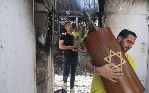 Israëliërs redden woensdagmorgen Torarollen uit een verbrande synagoge in Lod.beeld EPA, Abir Sultan