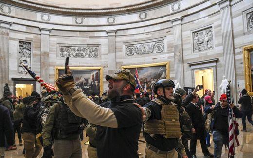 Oproerkraaiers met helmen en kogelwerende vesten bestormen op 6 januari het Capitool in Washington.beeld AFP, Saul Loeb