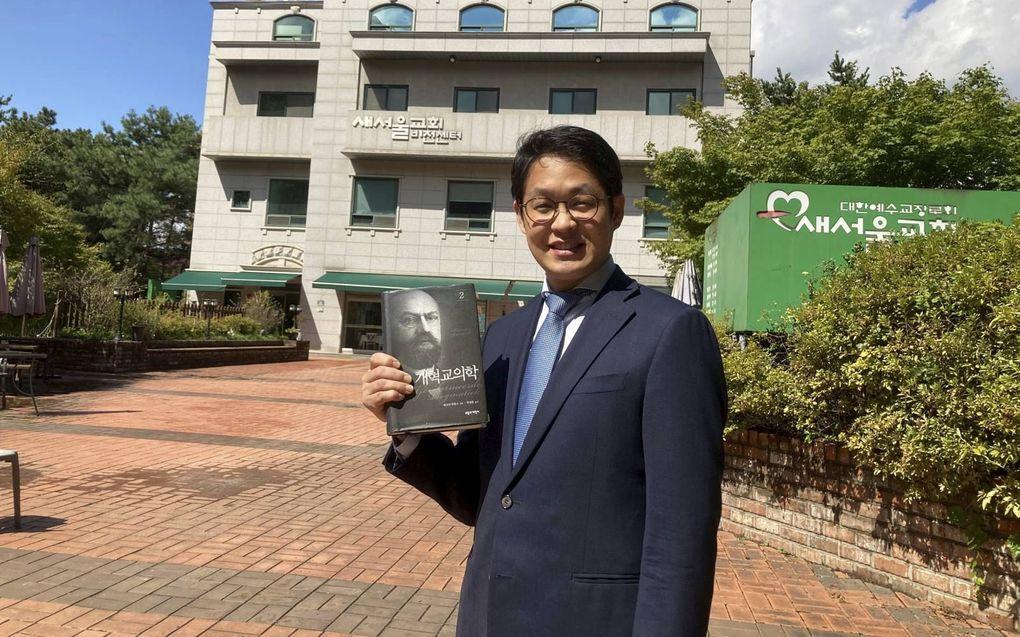 Changyun Choi voor zijn Saeseoul Church in Seoul. In zijn hand houdt hij de Koreaanse vertaling van een van de delen van de Gereformeerde Dogmatiek van Bavinck. beeld Changyn Choi