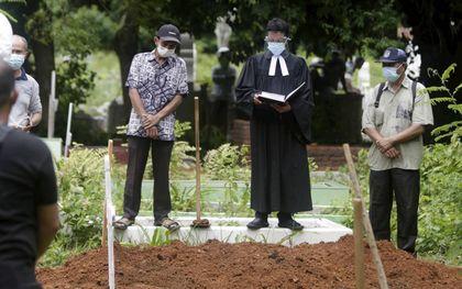 Een Indonesische predikant spreekt op het graf van een overleden coronapatiënt. Bijna alle landen op de wereld hadden de afgelopen anderhalf jaar te maken met hogere sterfte tijdens de pandemie. beeld EPA, Hotli Simanjuntak