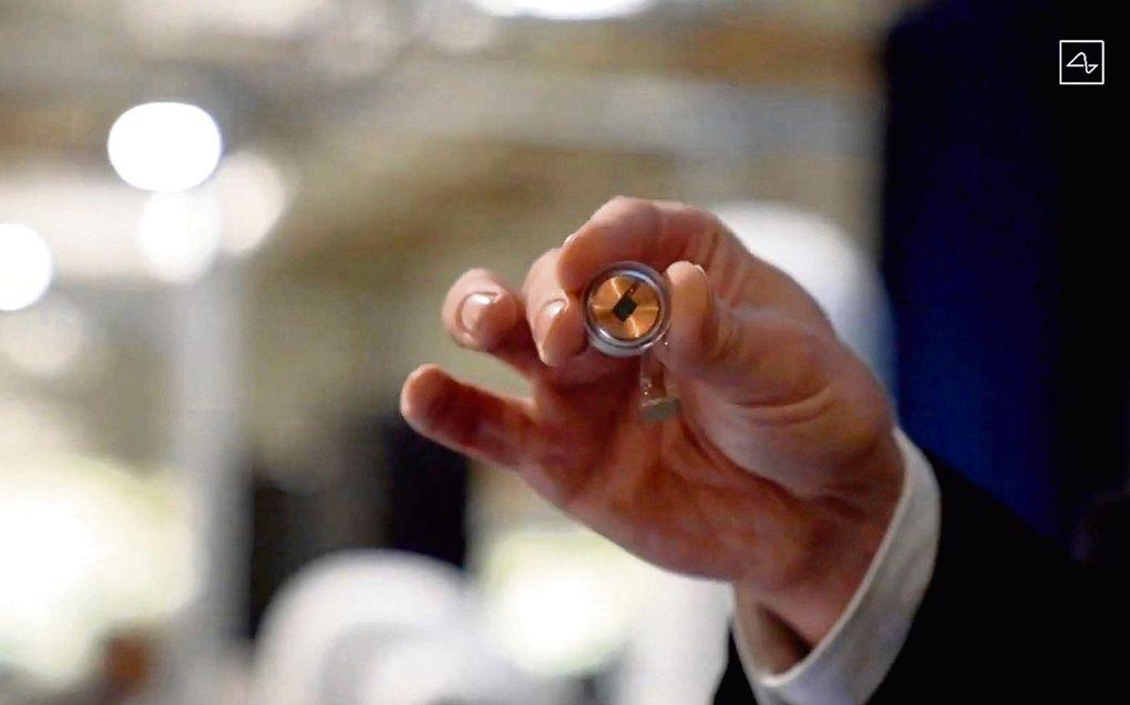 Elon Musk, de baas van het Amerikaanse bedrijf Neuralink, laat een chip zien, zoals hij die laat inbouwen in apen en varkens.beeld AFP, Neuralink
