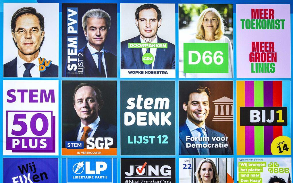 Medewerkers plaatsen een verkiezingsbord voor de Tweede Kamerverkiezingen op het Buitenhof in Den Haag. De verkiezingen vinden plaats op 17 maart. beeld ANP REMKO DE WAAL