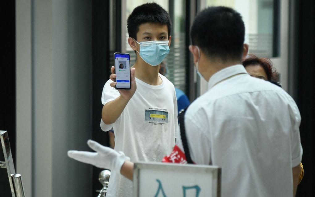Een man toont zijn toegangsbewijs in een winkelcentrum in Peking. beeld AFP, WANG Zhao