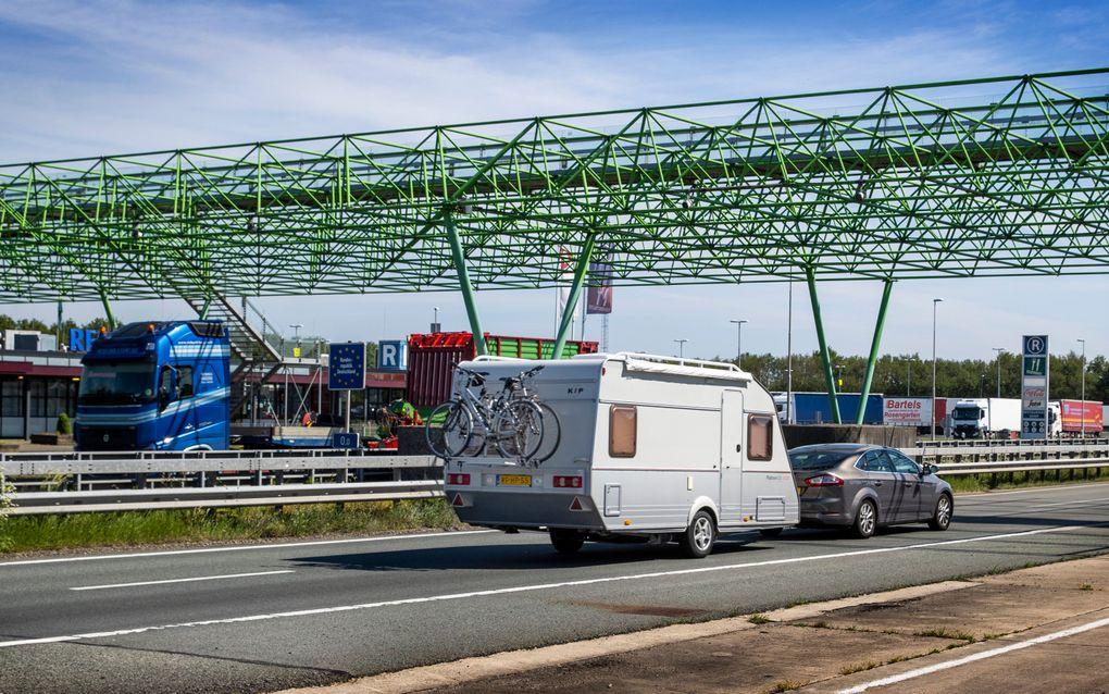 Vakantiegangers passeren de Nederlands-Duitse grens tussen De Lutte en het Duitse Bad Bentheim over de Duitse autobahn. beeld ANP VINCENT JANNINK