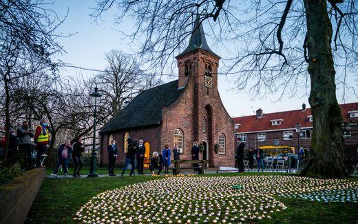 Waxinelichtjes branden tijdens de herdenking van coronaslachtoffers in de Hasseltse Kapel. Tilburg staat stil bij het uitbreken van de coronapandemie in Nederland, precies een jaar geleden. beeld ANP, ROB ENGELAAR