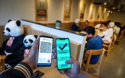 Bezoekers tonen voorafgaand aan hun bezoek aan een chinees restaurant hun coronatoegangsbewijs. beeld ANP, EVERT ELZINGA
