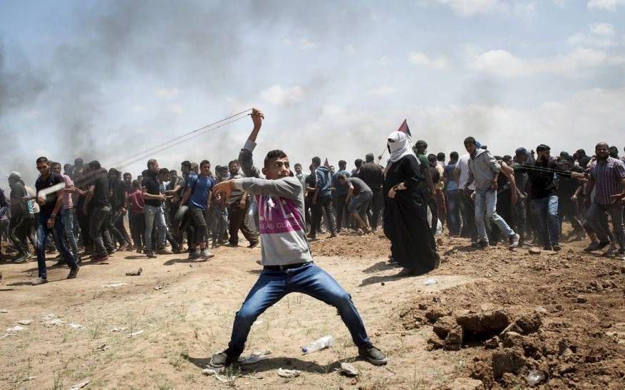 Een Palestijnse betoger slingerde maandag een steen richting Israëlische soldaten bij de grens tussen de Gazastrook en Israël. Bij confrontaties rond de grens zouden gisteren zeker 58 doden zijn gevallen.beeld EPA, Luca Piergiovanni